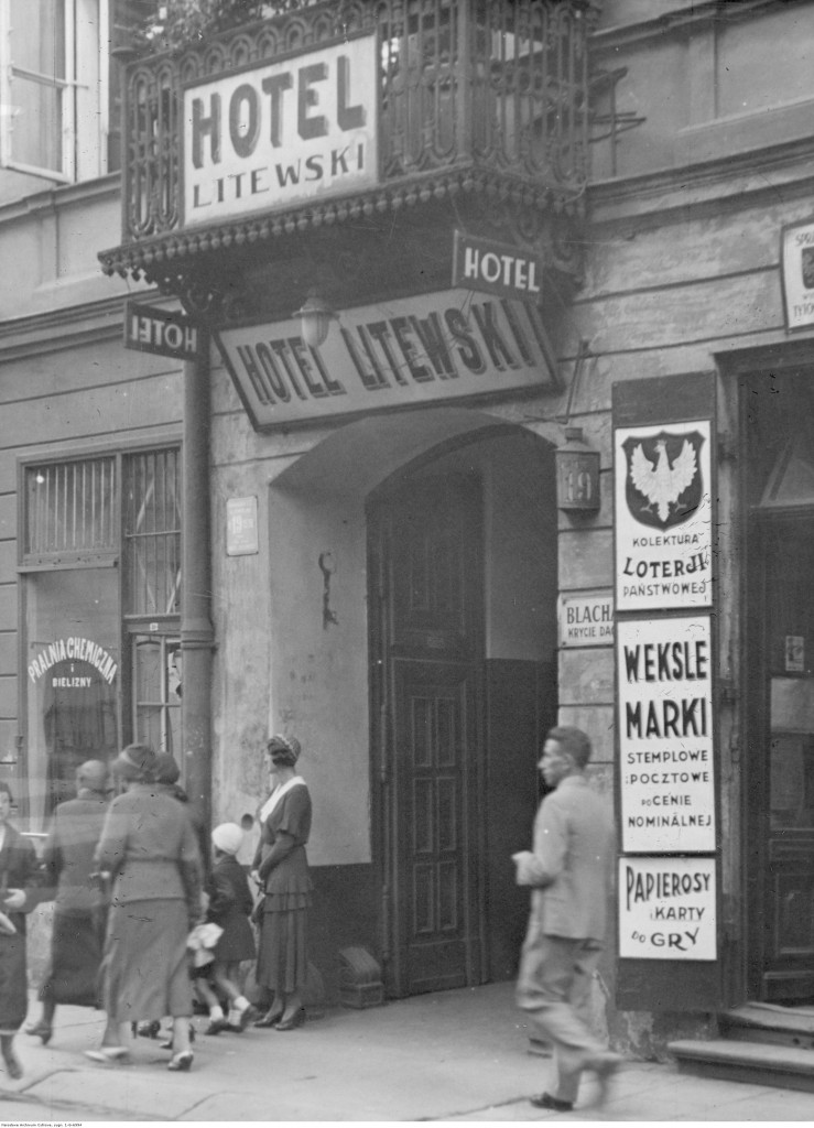 Fragment budynku z wejściem do hotelu przy ulicy Chmielnej 19. Widoczne szyldy reklamowe, 1932
